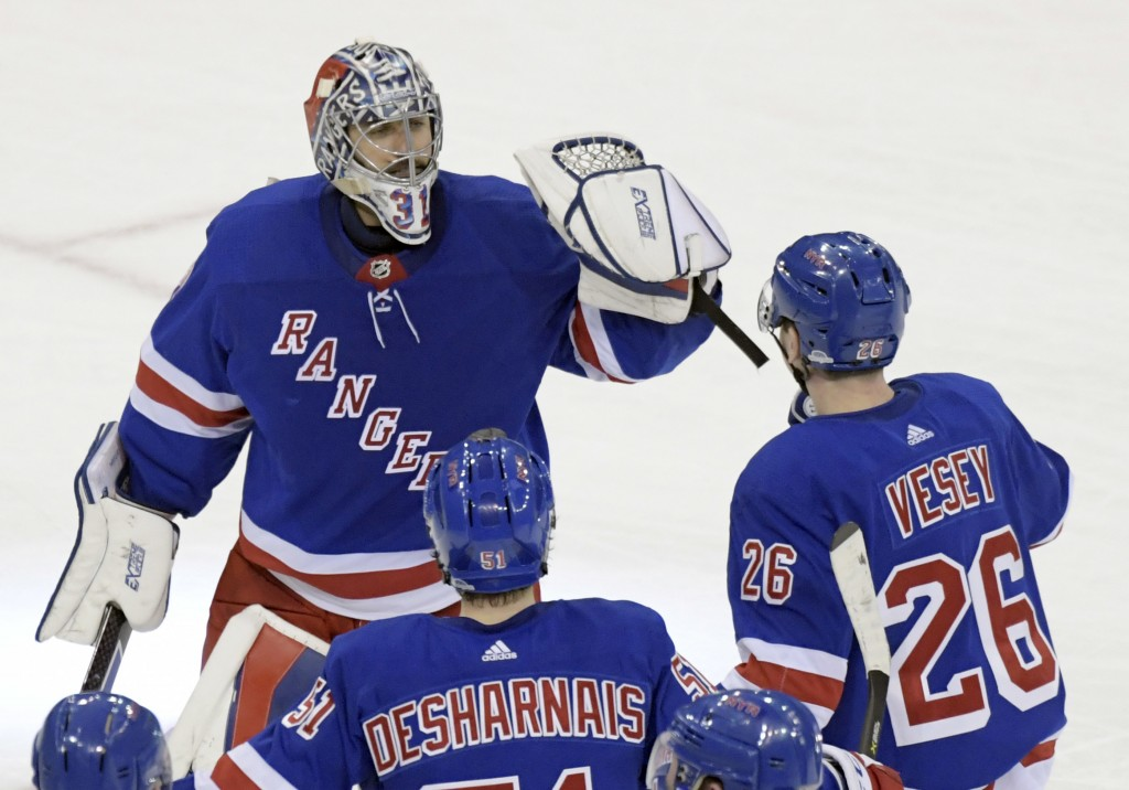 New York Rangers goalie Ondrej Pavelec (31) celebrates with left wing Jimmy Vesey (26) and center David Desharnais (51) after the Rangers defeated the...