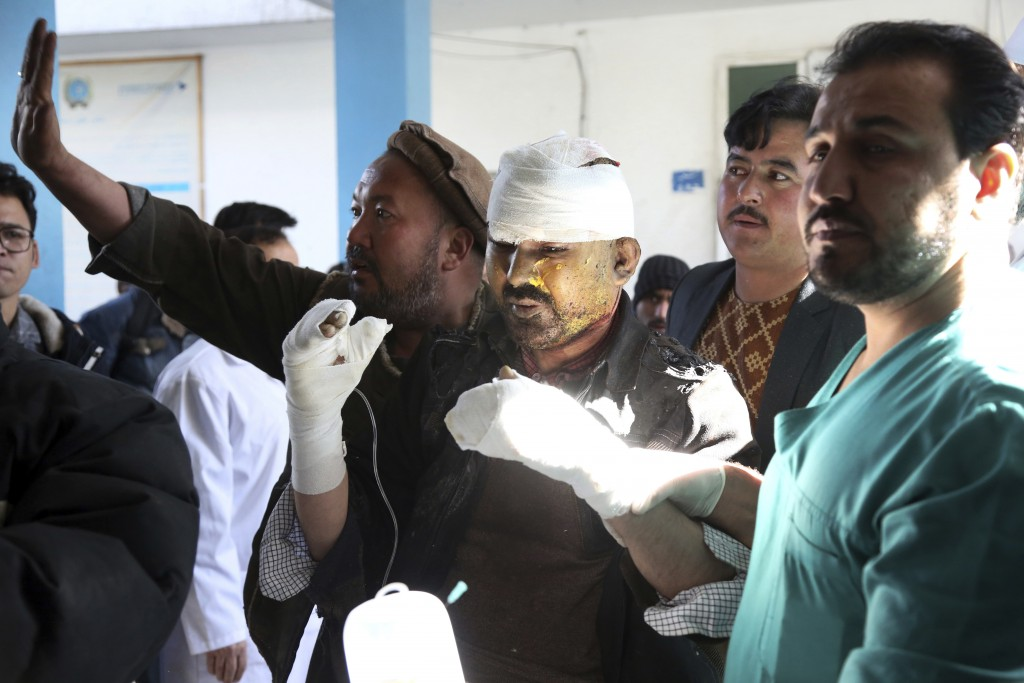 People carry an injured man into the hospital follwoing a suicide attack in Kabul, Afghanistan, Thursday, Dec. 28, 2017. Authorities say two simultane...