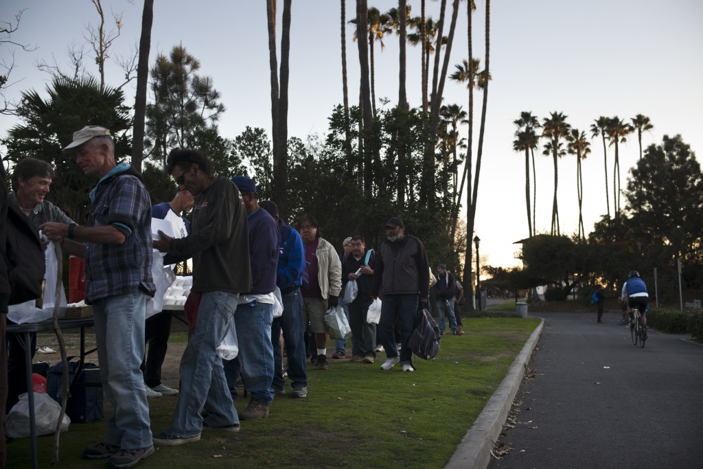 Homeless people wait in line for a free meal Thursday, Dec. 21, 2017, in Dana Point, Calif. The number of homeless living in Orange County has climbed...