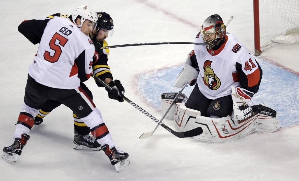 Ottawa Senators defenseman Cody Ceci (5) tries to clear away Boston Bruins left wing Brad Marchand as Senators goalie Craig Anderson (41) makes the sa...