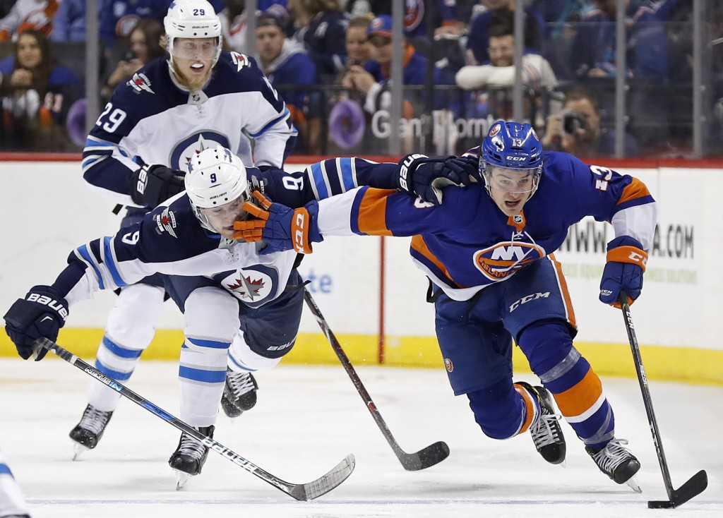 File- This Dec. 23, 2017, file photo shows New York Islanders center Mathew Barzal, right,  controlling  the puck against Winnipeg Jets center Andrew ...