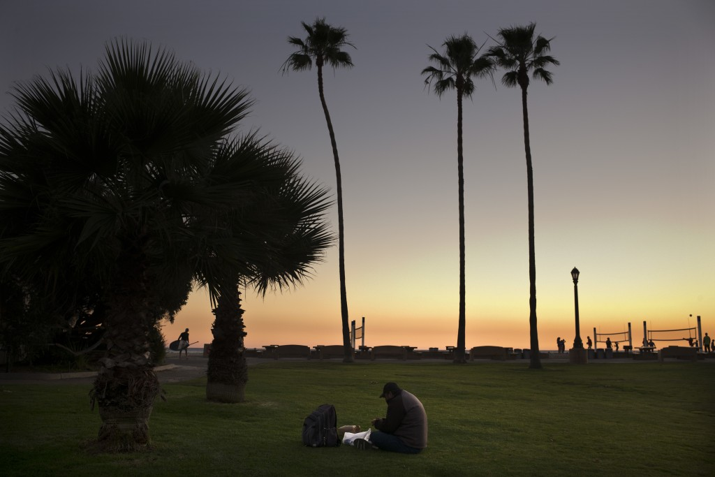 Sitting on the lawn at Doheny State Beach, Gholamreza Hagihgih, a 59-year-old Iranian immigrant who has been homeless for 20 years, eats his meal prov...