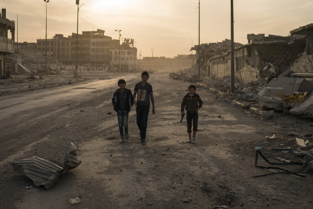 In this Nov. 15, 2017 photo, boys, one of them carrying a toy gun, walk on the empty streets of the Old City, in Mosul, Iraq. The cost to rebuild afte...