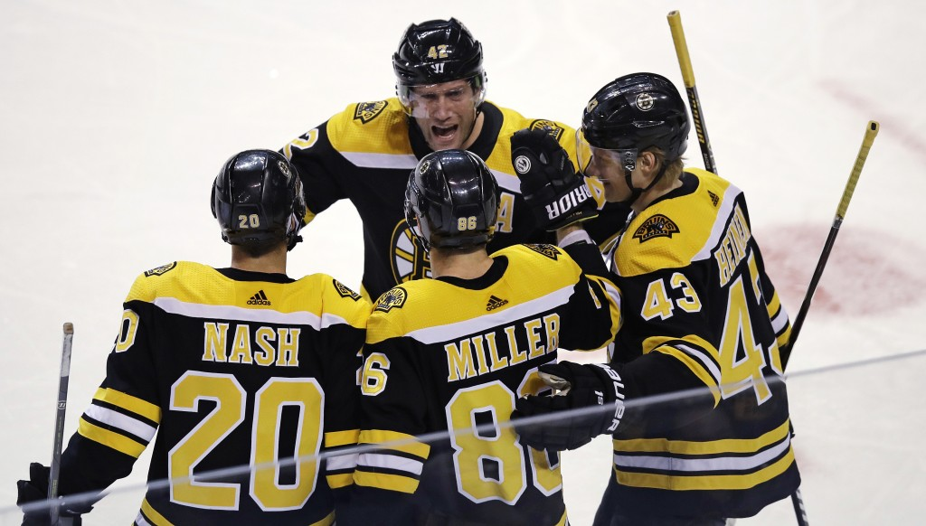 Boston Bruins defenseman Kevan Miller (86) is congratulated after his goal during the first period of an NHL hockey game against the Ottawa Senators i...