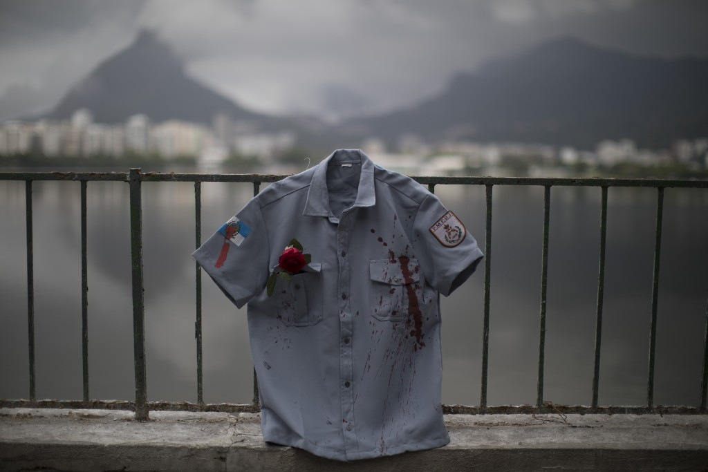 A police uniform shirt, stained in red representing spilt blood, hangs on a fence during a demonstration promoted by the NGO Rio de Paz, in Rio de Jan...