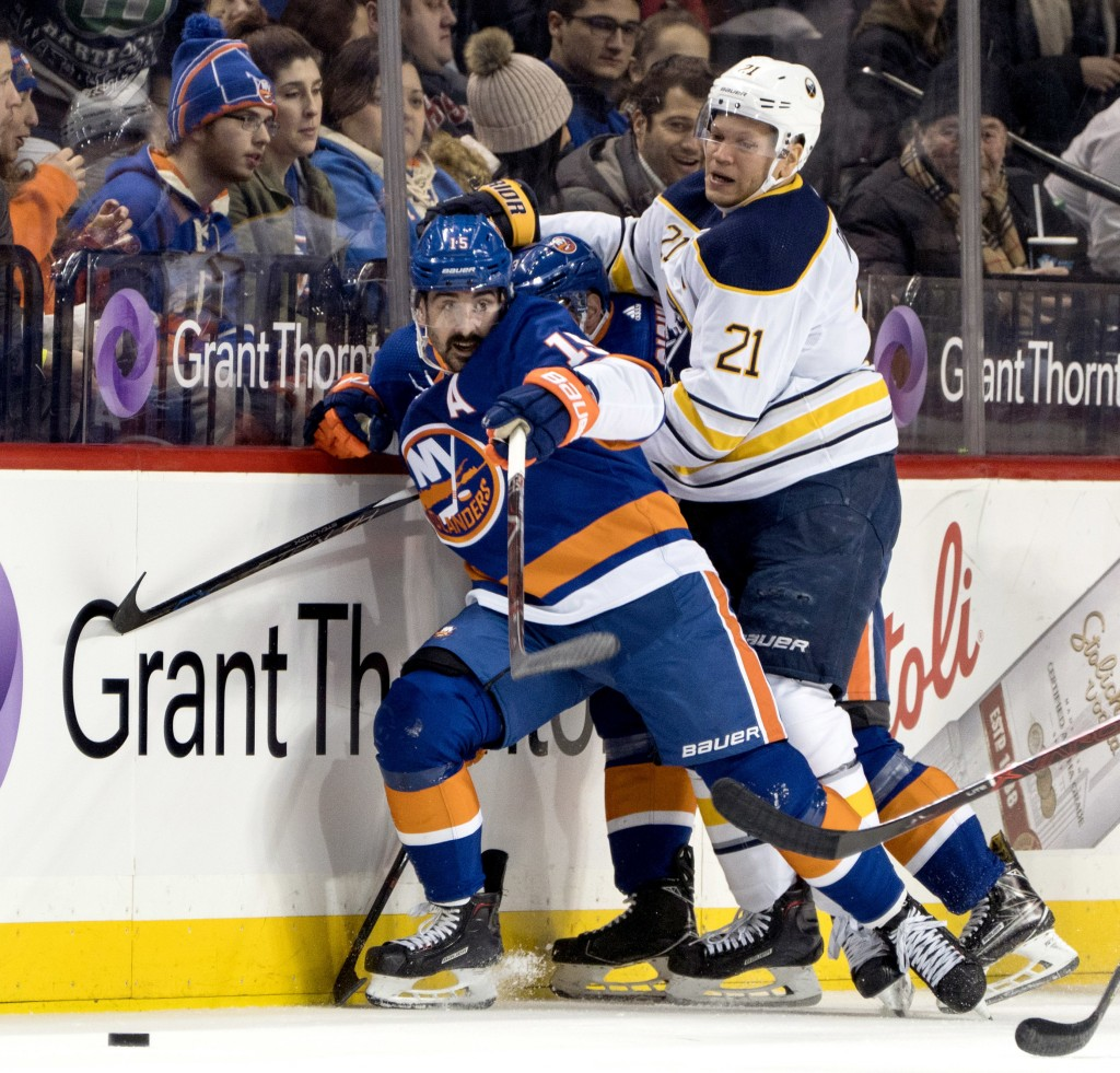 New York Islanders' Cal Clutterbuck slams in to the boards along with the Buffalo Sabres' Kyle Okposo as they go for the puck during the first period ...
