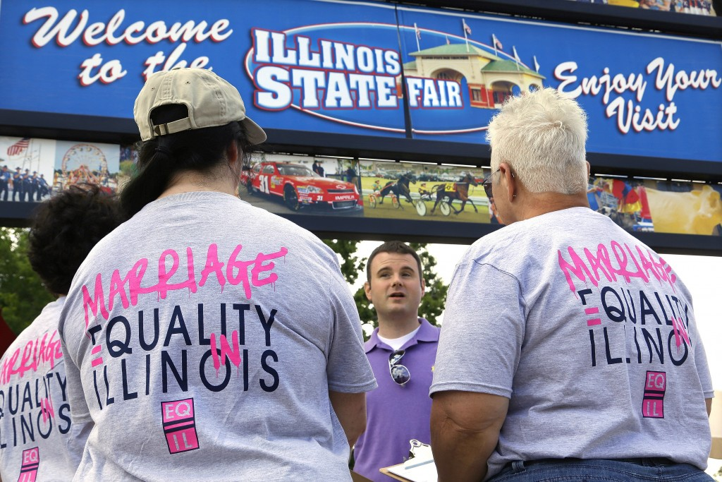 FILE - In this Wednesday, Aug. 14, 2013 file photo, Randy Hannig of Equality Illinois, hands out shirts supporting gay marriage at the Illinois State ...