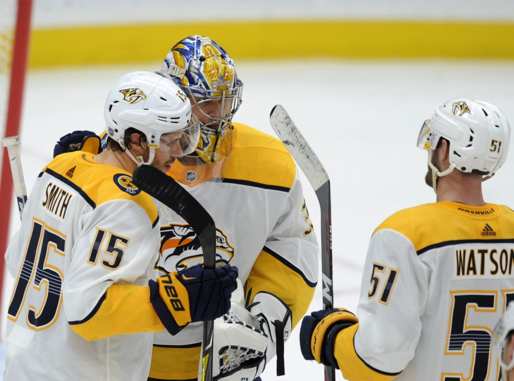 Nashville Predators goalie Pikka Rinne, center, of Finland, is congratulated by teammates Craig Smith (15) and Austin Watson (51) after their victory ...