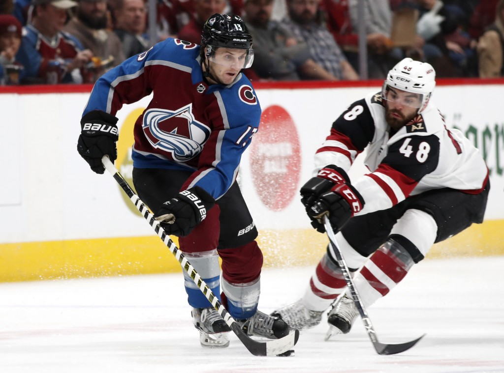 Colorado Avalanche center Alexander Kerfoot, left, picks up the puck in front of Arizona Coyotes left wing Jordan Martinook in the second period of an...