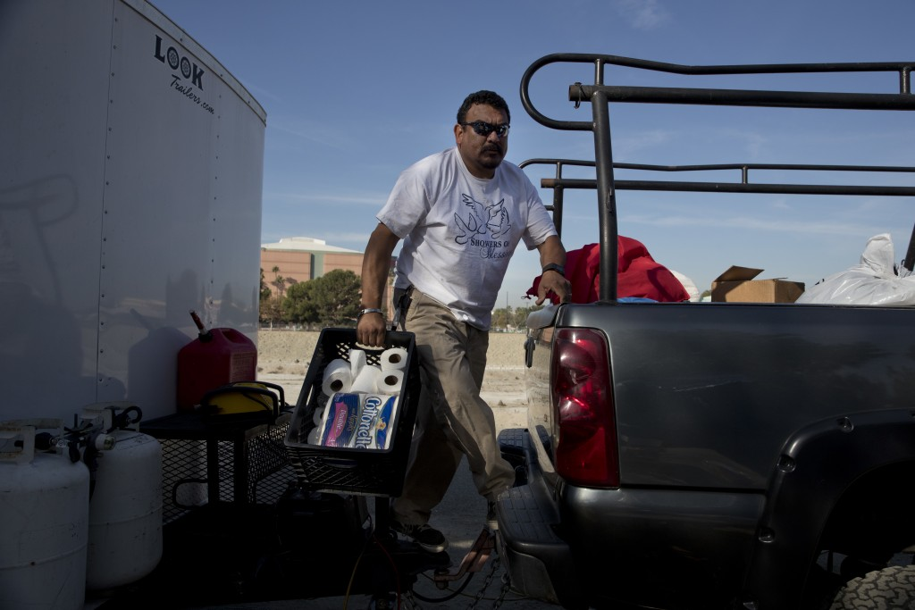 Armando Olvera, 49, who has been providing mobile showers for the homeless since 2010, gives out rolls of toilet paper to homeless people while operat...
