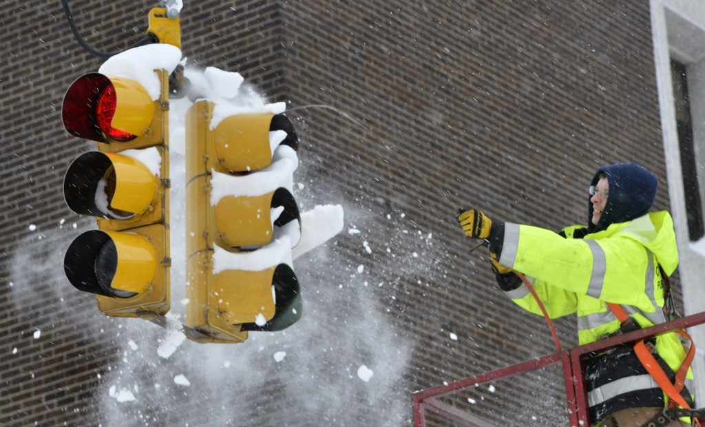 City of Erie traffic engineering employee Chuck Carnes Jr. uses compressed air to clear snow from a traffic signal in Erie, Pa., Wednesday, Dec. 27, 2...