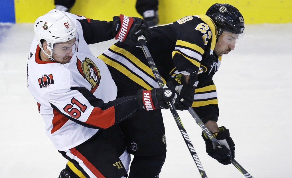 Ottawa Senators right wing Mark Stone (61) checks Boston Bruins left wing Brad Marchand (63) during the first period of an NHL hockey game in Boston, ...
