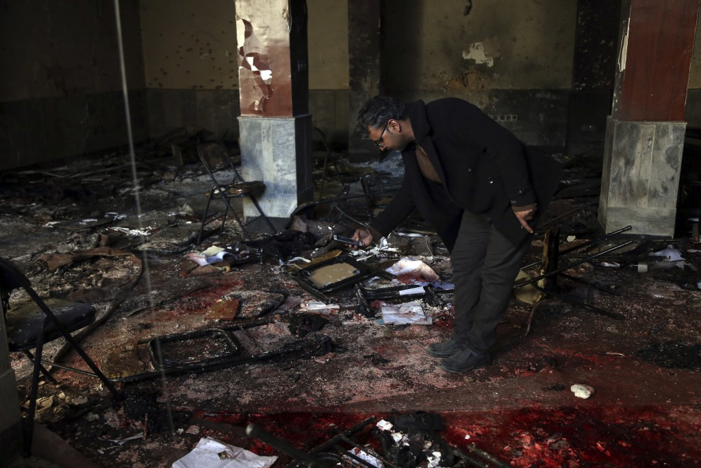 An Afghan man takes a photograph at the scene of a suicide attack on a Shiite cultural center in Kabul, Afghanistan, Thursday, Dec. 28, 2017. (AP Phot...