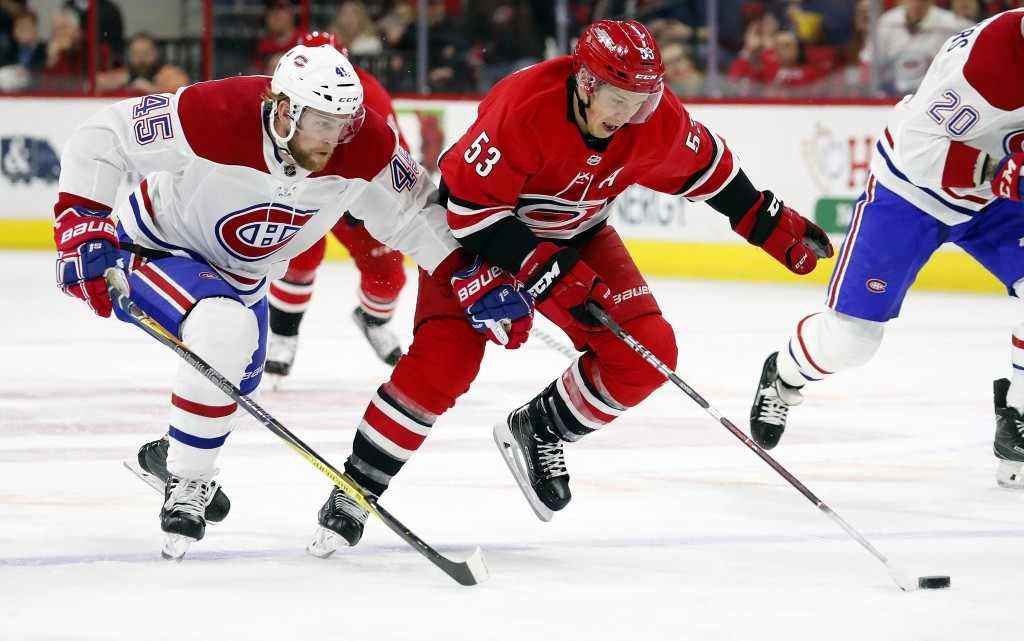 Carolina Hurricanes' Jeff Skinner (53) pushes the puck with Montreal Canadiens' Joe Morrow (45) nearby during the second period of an NHL hockey game,...