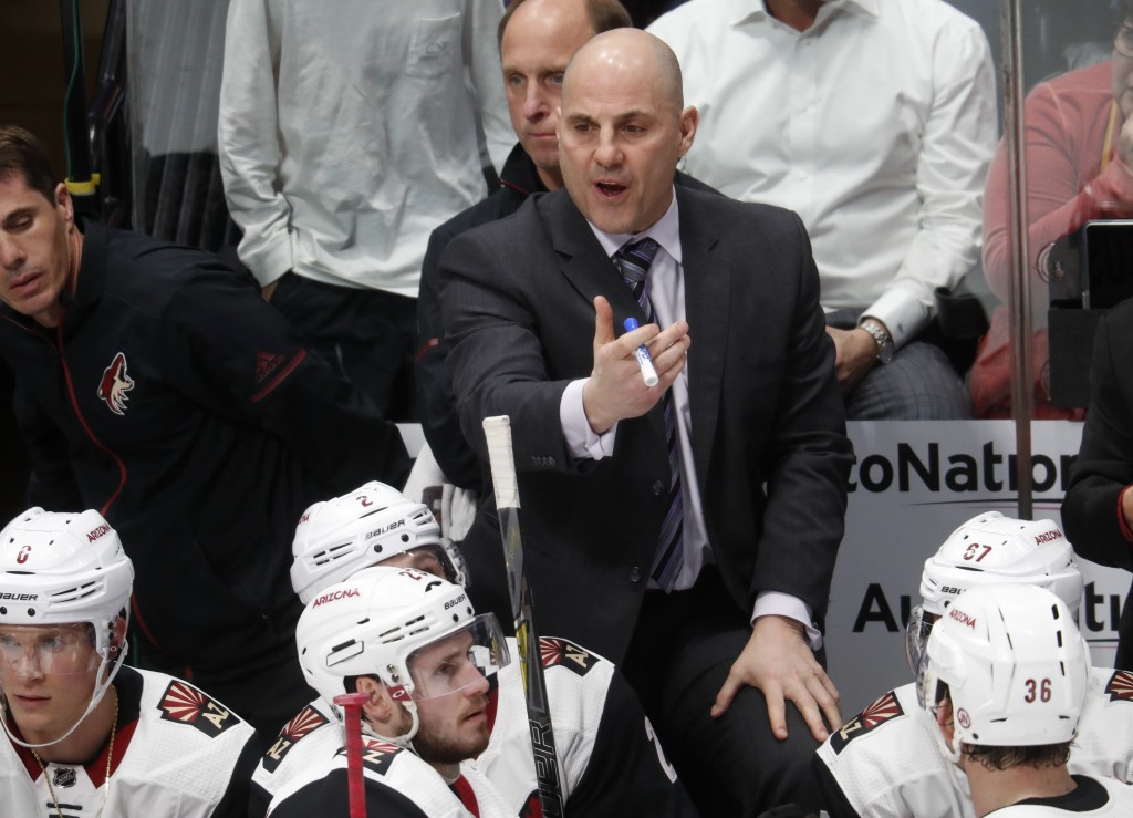 Arizona Coyotes coach Rick Tocchet talks to player during a timeout in the third period of the team's NHL hockey game against the Colorado Avalanche o...