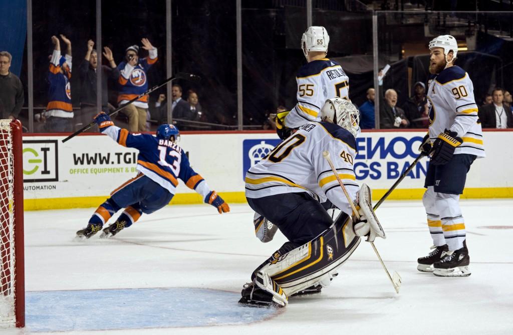 New York Islanders' Mathew Barzal (13) skates away from Buffalo Sabres' goalie Robin Lehner (40) after scoring the winning goal in overtime during an ...