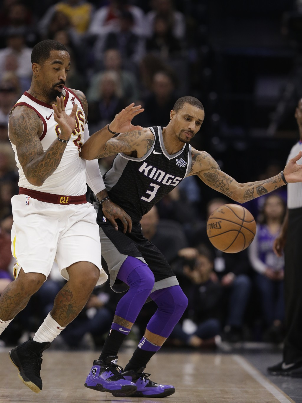 Cleveland Cavaliers guard J.R. Smith, left, and Sacramento Kings guard George Hill chase after the ball as it goes out of bounds during the first quar...