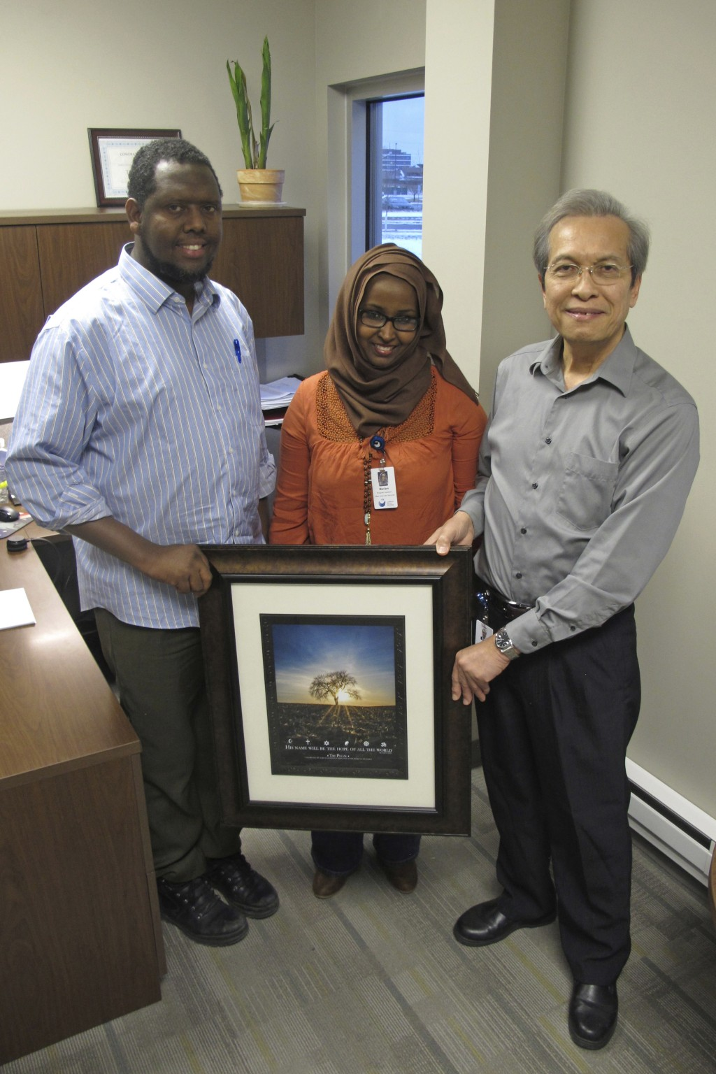 In this Dec. 15, 2017 photo, Tri Phan, right, poses with fellow Lutheran Social Services staff members Abdiwali Sharif-Abdinasir and Mariam Bassoma at...