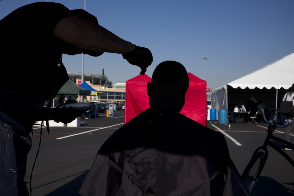 A homeless man, who declined to give his name, gets a free haircut in the parking lot of Angel Stadium during the community outreach day Tuesday, Dec....
