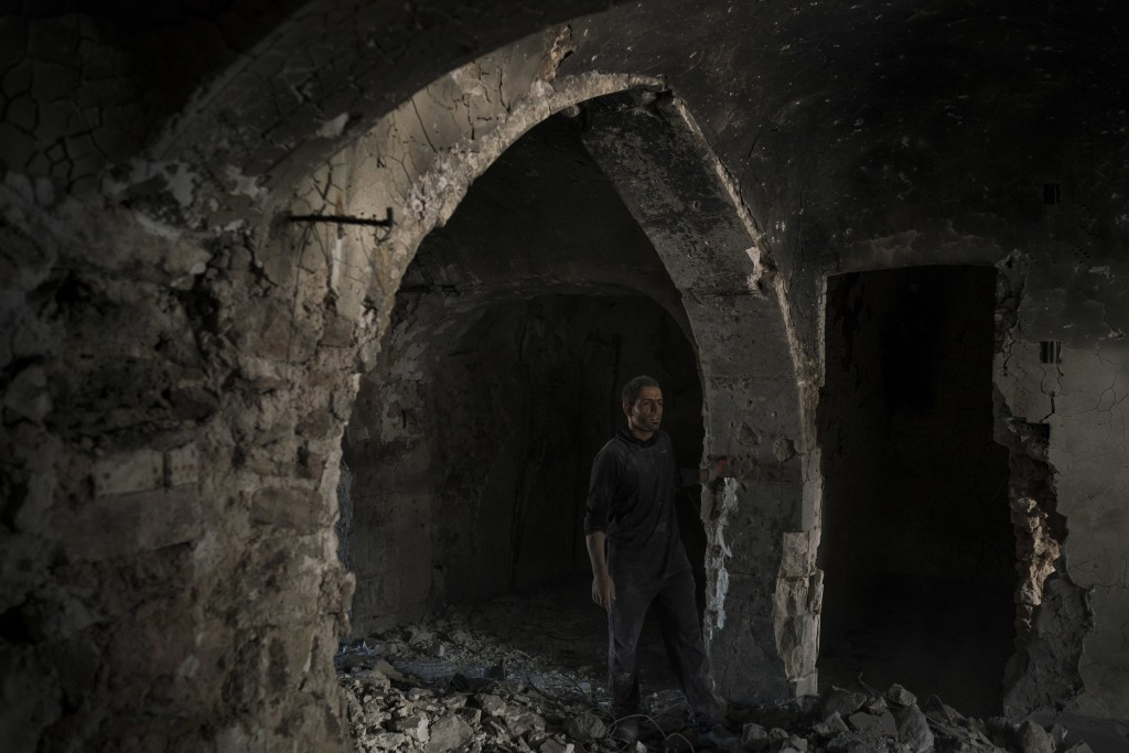 In this Nov. 14, 2017 photo, a construction worker stands in the destroyed old bazaar in the Old City of Mosul, Iraq. The scope of destruction in the ...