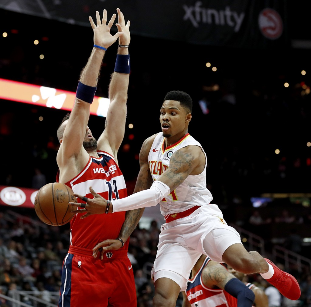 Atlanta Hawks' Kent Bazemore, right, passes the ball behind the back of Washington Wizards' Marcin Gortat, of Poland, in the first quarter of an NBA b...