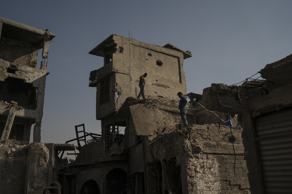 In this Nov. 18, 2017 photo, construction workers stand atop damaged buildings and shops in the Old City of Mosul, Iraq. The scope of destruction in t...