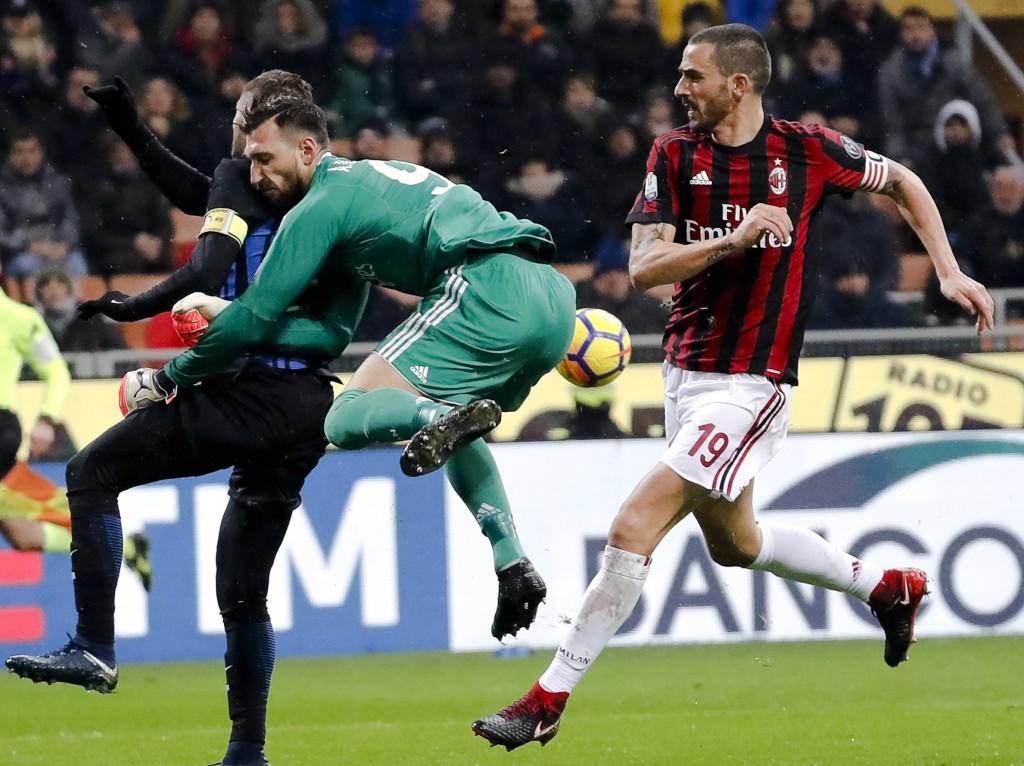 AC Milan goalkeeper Antonio Donnarumma, center, blocks Inter Milan's Mauro Icardi, left, as teammate Leonardo Bonucci, right, defends during an Italia...