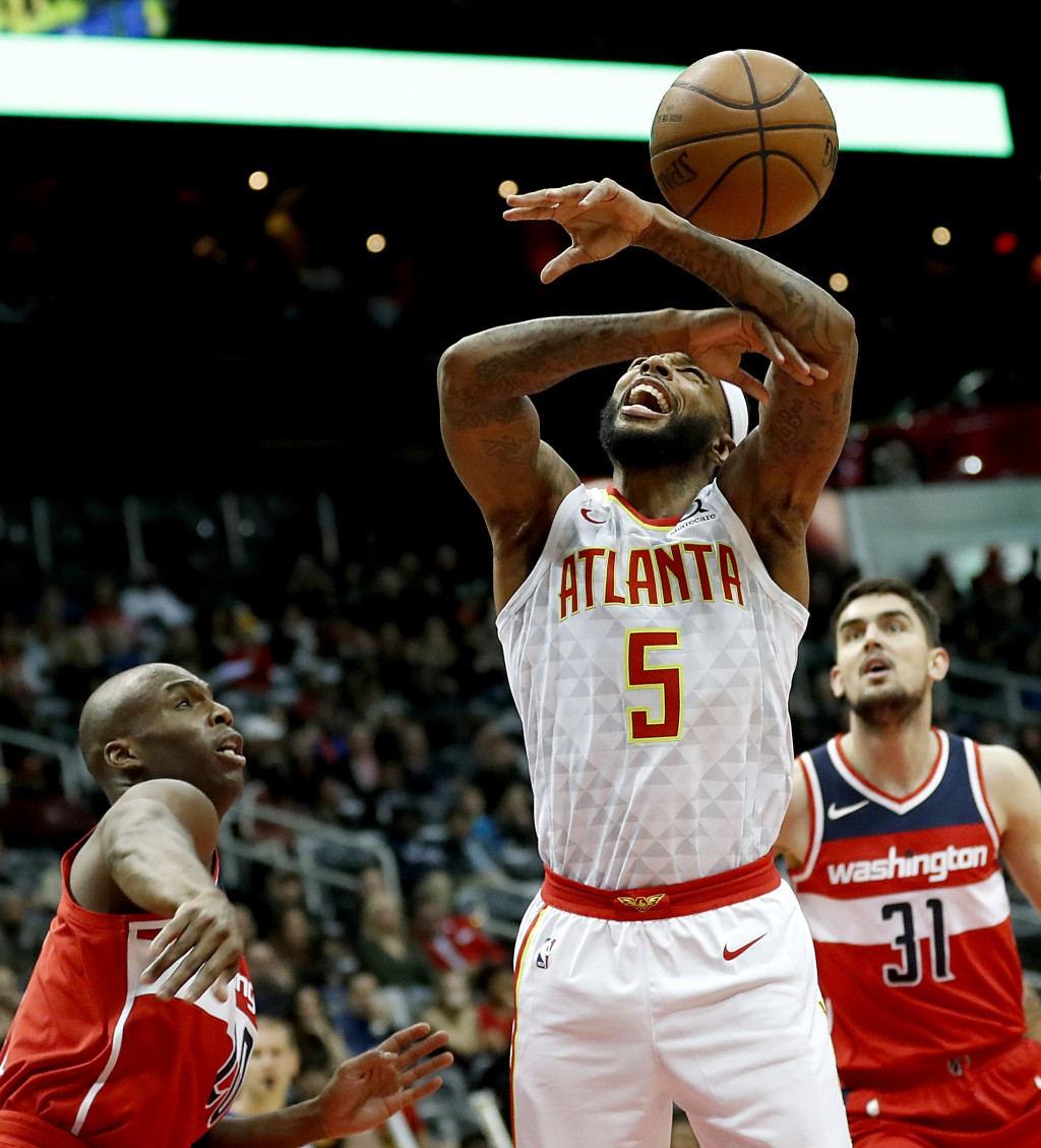 Atlanta Hawks' Malcolm Delaney (5) is fouled by Washington Wizards' Jodie Meeks, left, in the second quarter of an NBA basketball game in Atlanta, Wed...