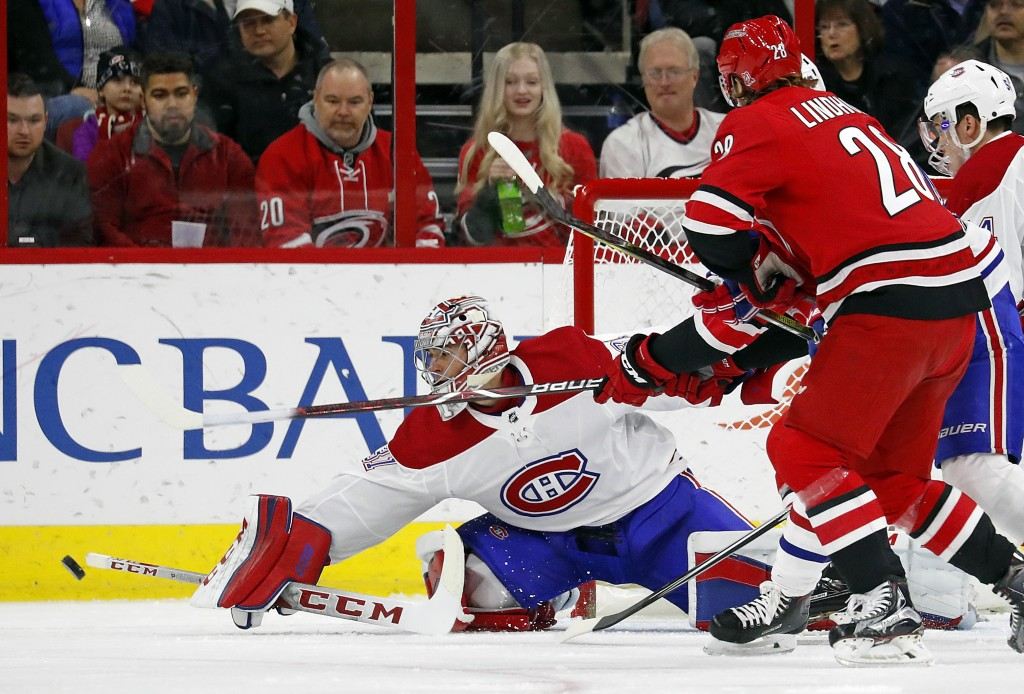 Montreal Canadiens goalie Carey Price, front left, clears a shot by Carolina Hurricanes' Elias Lindholm (28) during the first period of an NHL hockey ...