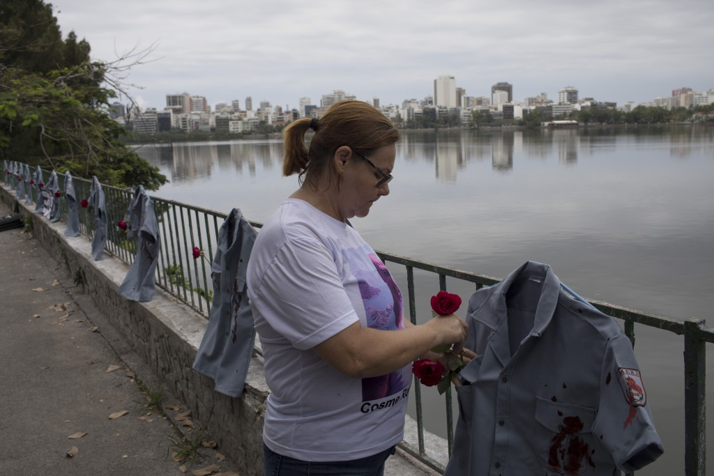 Vera Lucia Venin de Souza places a rose in a police uniform shirt, stained in red representing spilt blood, as it hangs on a fence during a demonstrat...