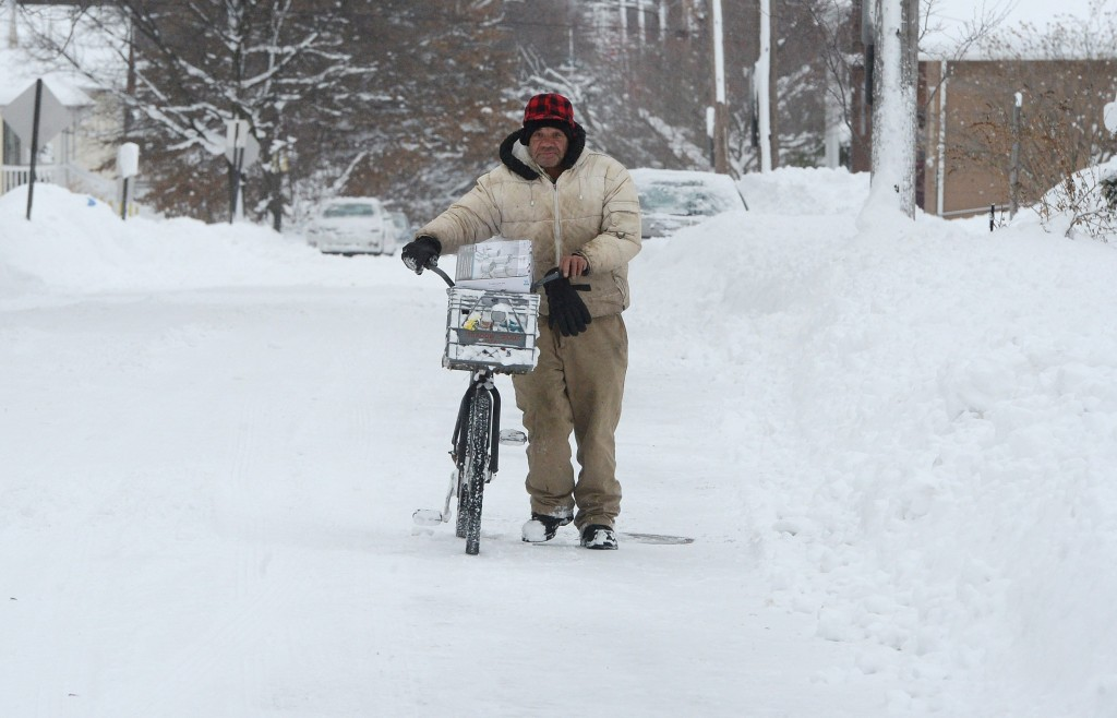 Logan Rogers pushes his bike along East Third Street in Erie, Pa., Wednesday, Dec. 27, 2017. Freezing temperatures and below-zero wind chills socked m...