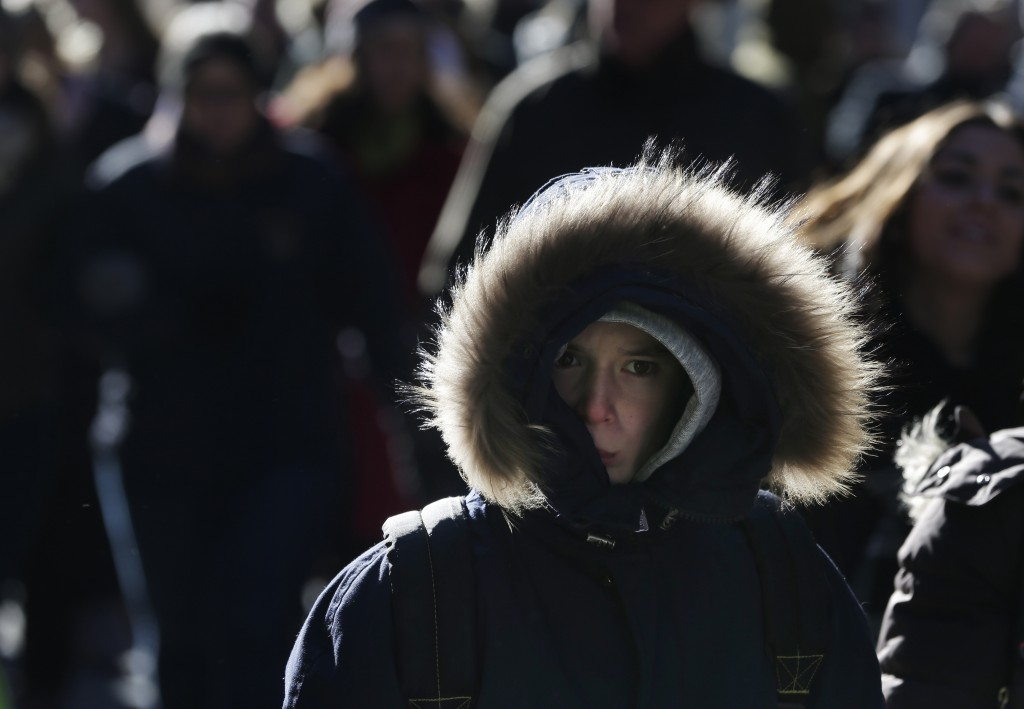 Pedestrians try to keep warm while walking in New York's Times Square, Wednesday, Dec. 27, 2017. Freezing temperatures and below-zero wind chills sock...