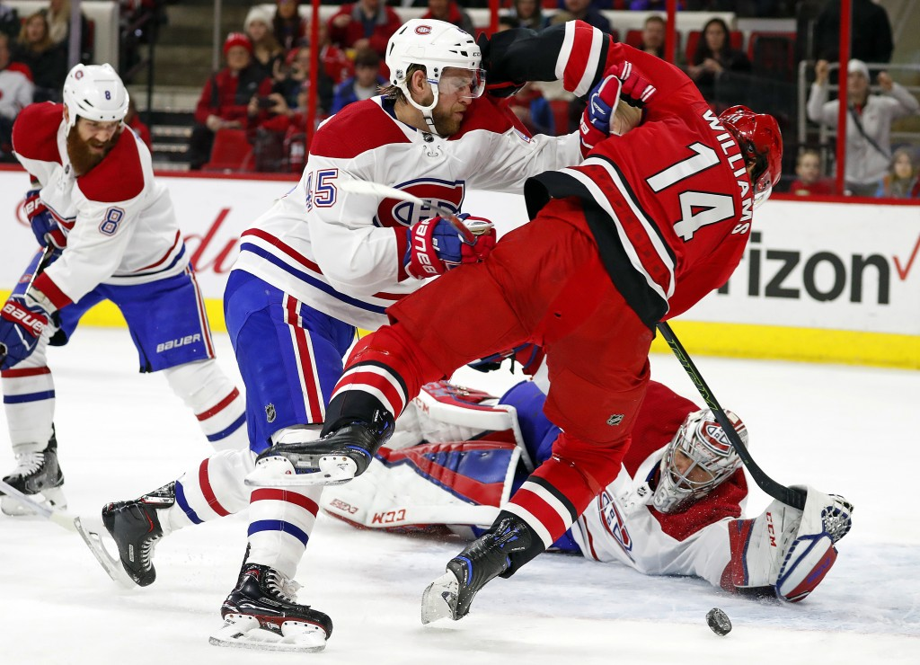 Montreal Canadiens' Joe Morrow (45) knocks Carolina Hurricanes' Justin Williams (14) off the puck in front of Canadiens goalie Carey Price (31) during...