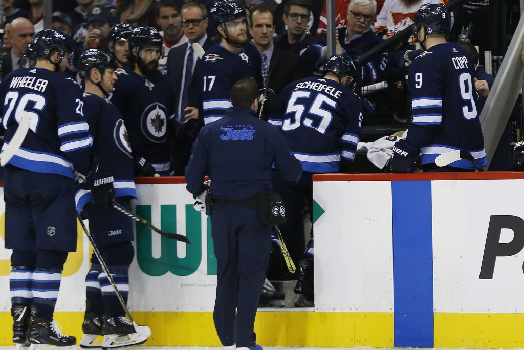 Winnipeg Jets' Mark Scheifele (55) is assisted off the ice during the second period of the team's NHL hockey game against the Edmonton Oilers on Wedne...