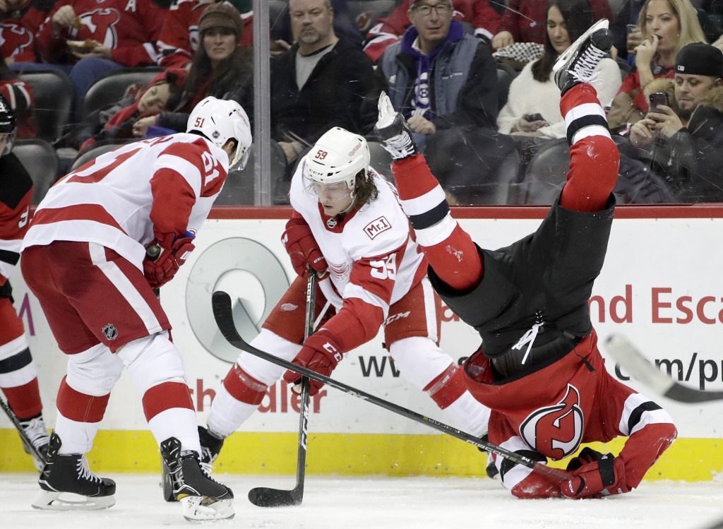 New Jersey Devils center Nico Hischier, right, of Switzerland, flips over while competing for the puck with Detroit Red Wings' Tyler Bertuzzi (59) and...