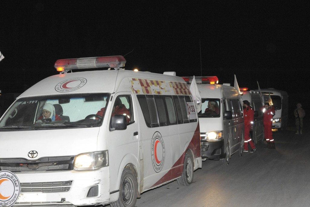 In this photo released by the Syrian official news agency SANA, members of the Syrian Arab Red Crescent gather near their ambulances during a human ev...