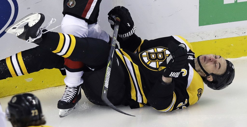 Boston Bruins defenseman Zdeno Chara (33) hits the ice hard on a check from Ottawa Senators right wing Bobby Ryan (9) during the first period of an NH...