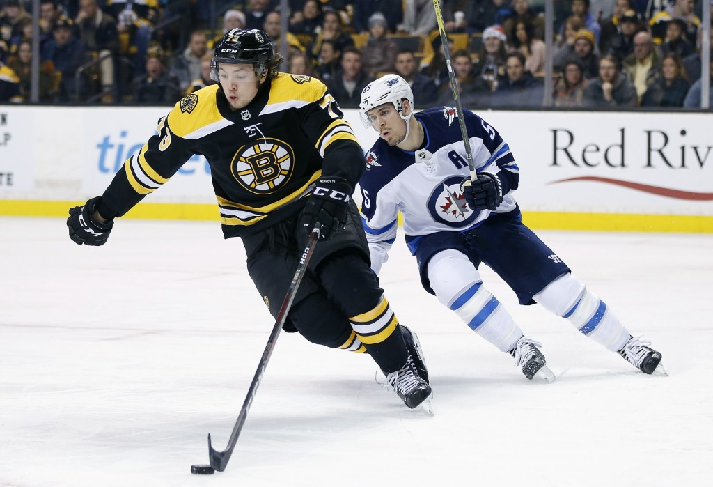 File-This Dec. 21, 2017, file photo shows Boston Bruins' Charlie McAvoy (73) handling the puck in front of Winnipeg Jets' Mark Scheifele (55) during t...