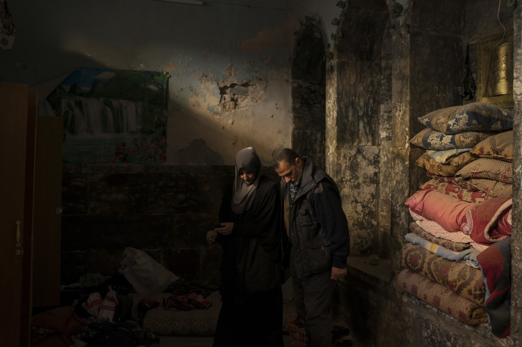 In this Nov. 16, 2017 photo, Yahya Ali, right and Haifa Shehab, look through the rubble in their house in the Old City of Mosul, Iraq. The U.N. estima...