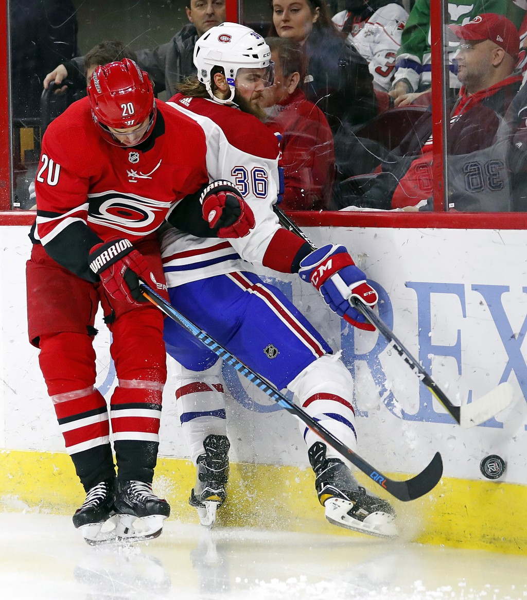 Carolina Hurricanes' Sebastian Aho (20) collides with Montreal Canadiens' Brett Lernout (36) during the second period of an NHL hockey game, Wednesday...