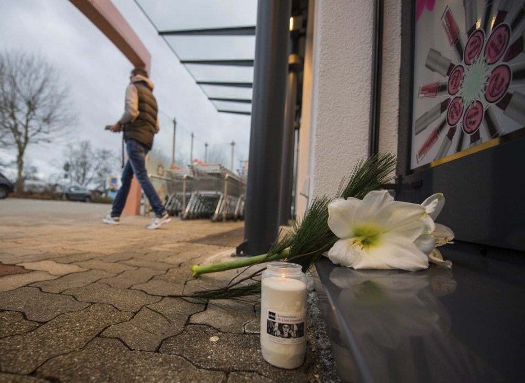 In this Dec. 27, 2017 photo. a customer leaves a drugstore in Kandel, Germany. Flowers and candles lie in front of the entrance. A 15-year-old Afghan ...