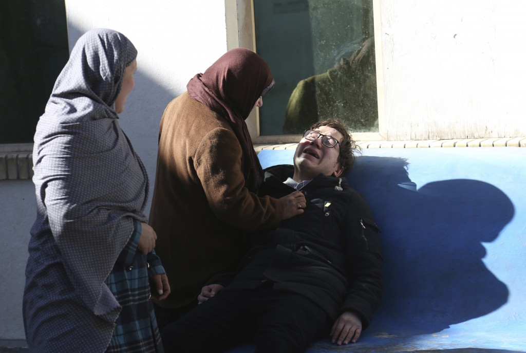 Two women console a man outside a hospital following a suicide attack in Kabul, Afghanistan, Thursday, Dec. 28, 2017. Authorities say attackers storme...