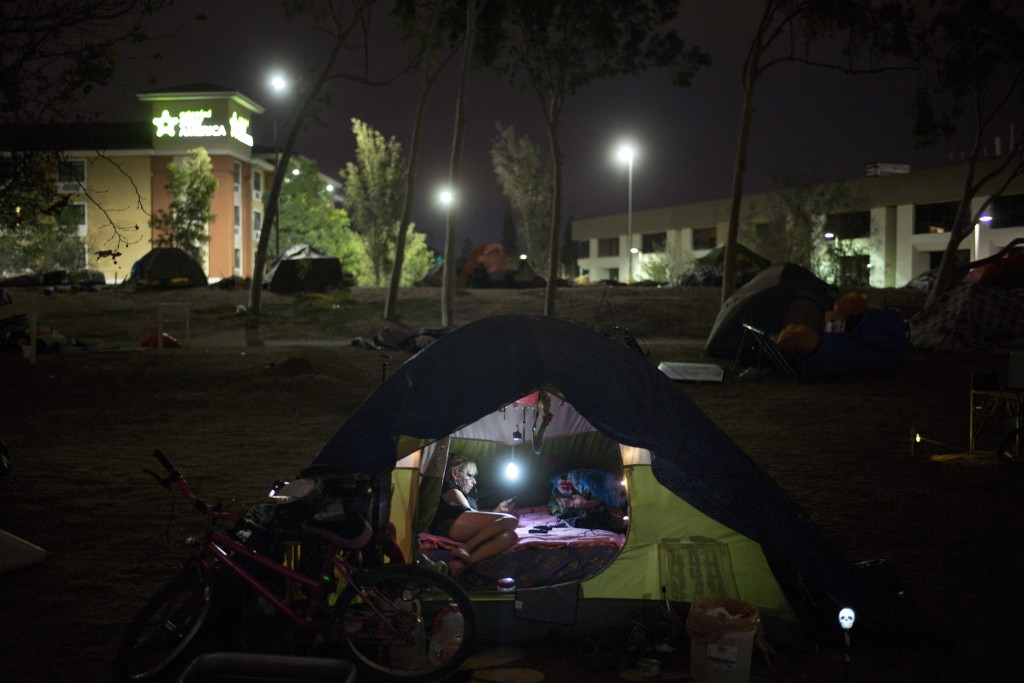 Homeless Jacqueline Anderson, 63, passes time playing with her smartphone in a homeless encampment on the Santa Ana River trail Sunday, Dec. 10, 2017,...