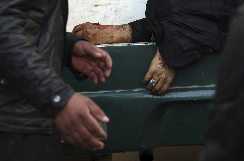 A man passes the hand of a deceased woman on a stretcher in a hospital following a suicide attack in Kabul, Afghanistan, Thursday, Dec. 28, 2017. Auth...