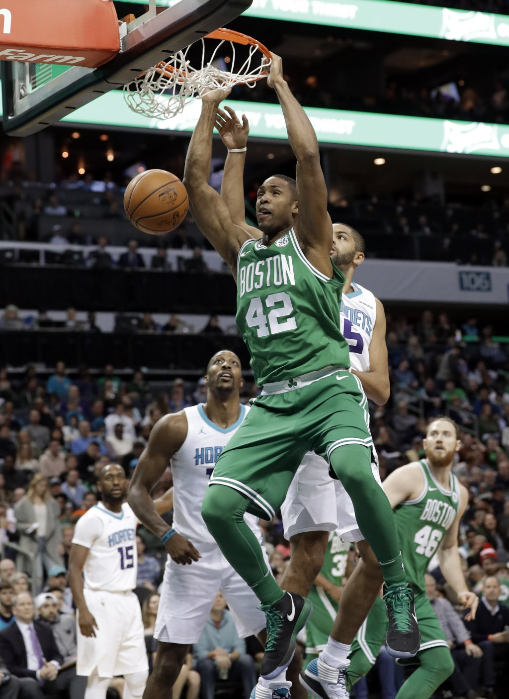 Boston Celtics' Al Horford (42) dunks past Charlotte Hornets' Nicolas Batum (5) during the first half of an NBA basketball game in Charlotte, N.C., We...