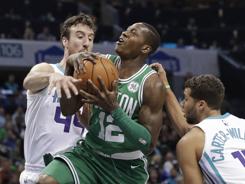 Boston Celtics' Terry Rozier (12) is fouled as he drives between Charlotte Hornets' Frank Kaminsky (44) and Michael Carter-Williams (10) during the fi...