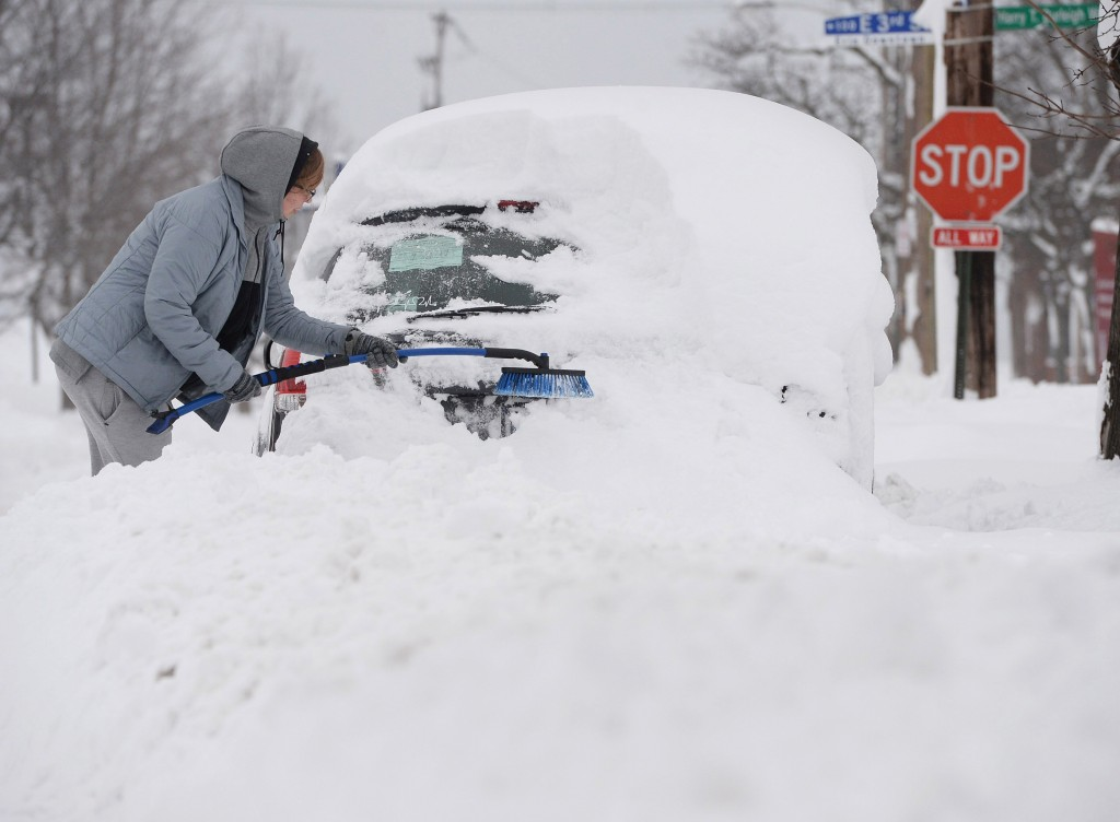 Chelse Volgyes clears snow from her car in Erie, Pa., Wednesday, Dec. 27, 2017. Freezing temperatures and below-zero wind chills socked much of the no...