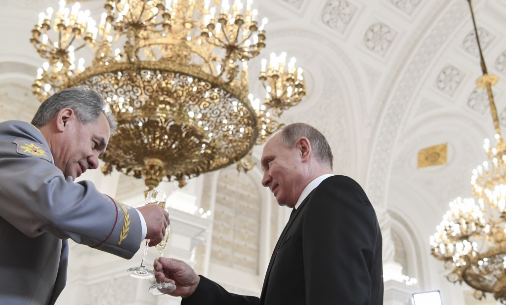 Russian President Vladimir Putin, right, makes a toast with Russian Defence Minister Sergei Shoigu during an award ceremony in the Kremlin, in Moscow,...