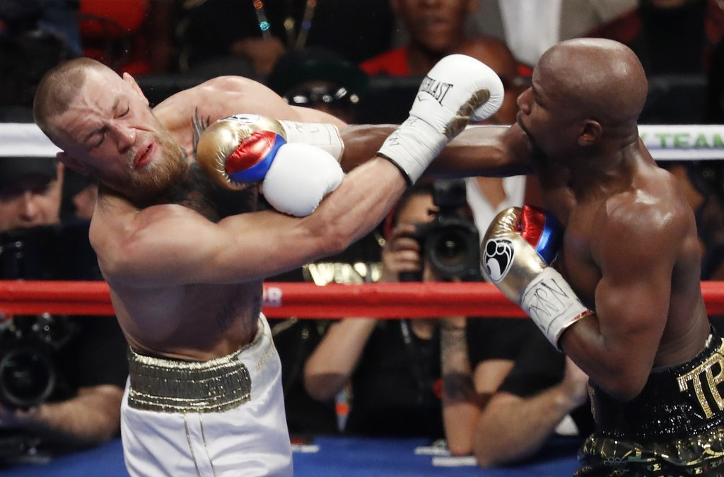 FILE - In this Aug. 26, 2017, file photo, Floyd Mayweather Jr., right, hits Conor McGregor during a super welterweight boxing match in Las Vegas. (AP ...