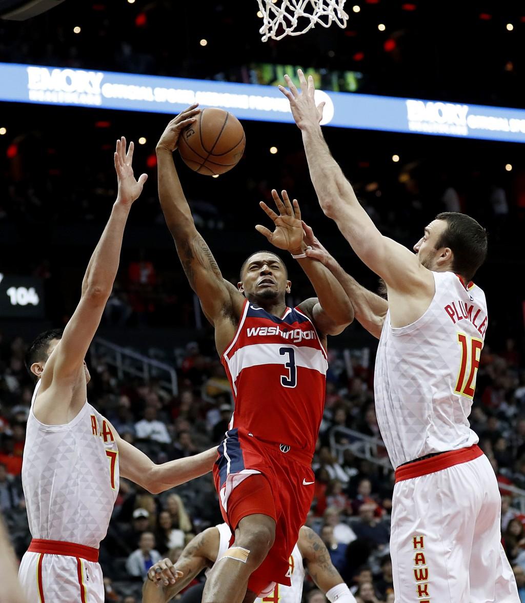 Washington Wizards' Bradley Beal, center, shoots against Atlanta Hawks' Ersan Ilyasova, left, of Turkey, and Miles Plumlee in the fourth quarter of an...